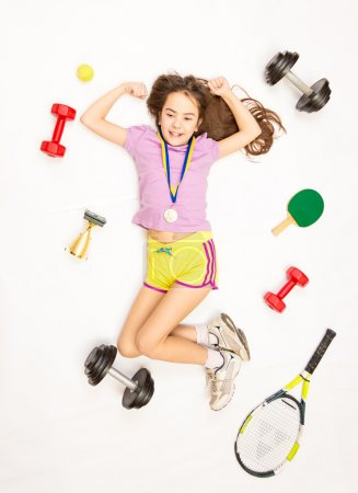 sporty girl posing with gold medal and sports equipment