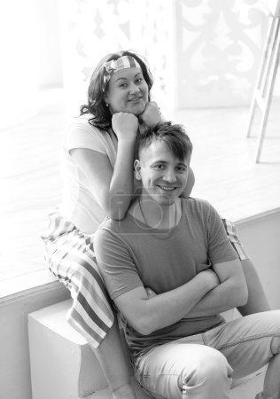 Foto de Retrato en blanco y negro de la mujer embarazada feliz abrazando marido de la espalda - Imagen libre de derechos