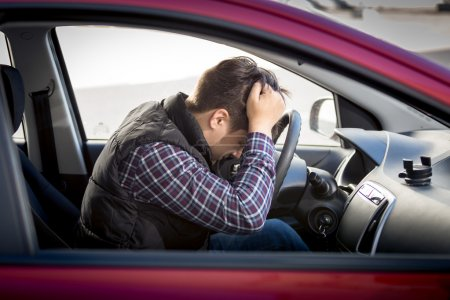 stressed man sitting on car drivers seat