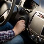 Closeup shot of man inserting key in car ignition ...