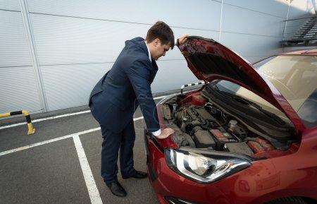 Photo pour Stressé jeune homme d'affaires regardant sous le capot de la voiture - image libre de droit