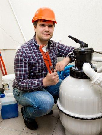 Photo pour Ingénieur de réparateur posant au système circulant de haute pression avec des pinces rouges - image libre de droit