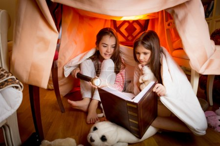Two sisters sitting in house made of blankets and reading book
