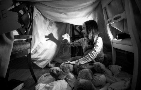 Photo pour Photo noire et blanche de la fille mignonne faisant l'ombre du crabot avec des mains et la lampe de poche - image libre de droit