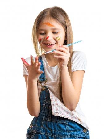 Photo pour Portrait isolé d'une petite fille souriante dessinant sur ses mains avec un pinceau - image libre de droit