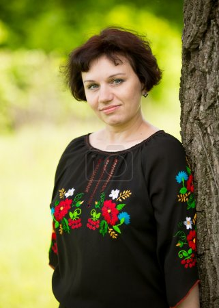 middle aged woman in traditional ukrainian shirt posing at meado