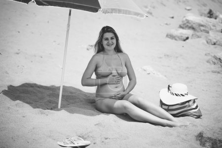 Black and white photo of cute pregnant woman sitting under paras