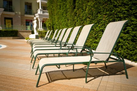 Row of sunbeds at poolside in luxurious hotel