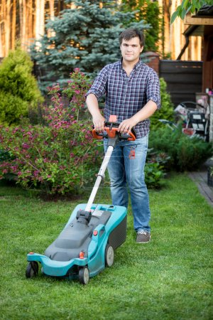 young man posing at backyard with lawn mower