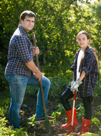 smiling man and cute girl digging soil at garden with shovels