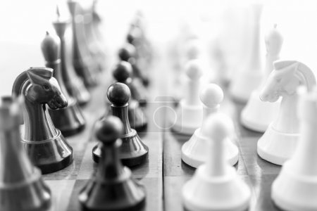 Black and white shot of chess pieces standing in rows face to fa