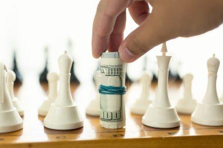 Photo pour Photo rapprochée de l'homme faisant mouvement dans le jeu d'échecs avec des billets tordus - image libre de droit