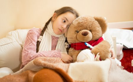 sick girl resting in bed with brown teddy bear