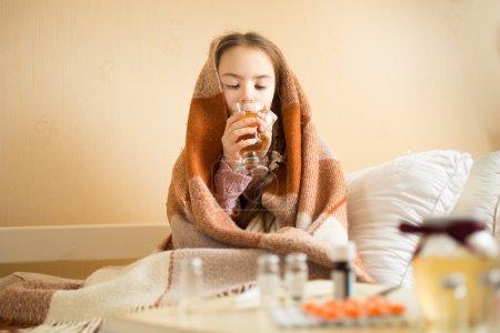 Photo pour Portrait de mignonne fille malade couvert de couverture boire du thé chaud - image libre de droit