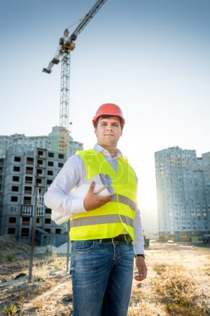 engineer in hardhat and yellow jacket posing with blueprints