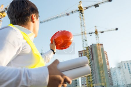 Photo for Closeup photo of engineer posing on building site with orange hardhat - Royalty Free Image