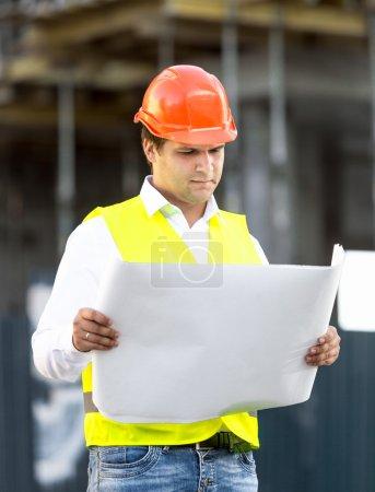 Photo pour Verticale de contremaître lisant des plans contre l'échafaudage au chantier de construction - image libre de droit
