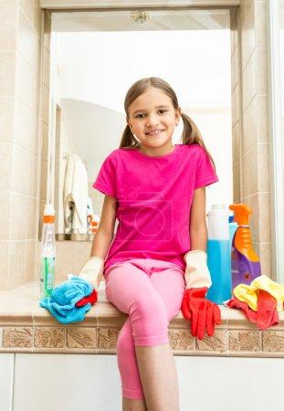 Photo pour Portrait de fille souriante assise sur l'évier à la salle de bain tout en faisant le nettoyage - image libre de droit