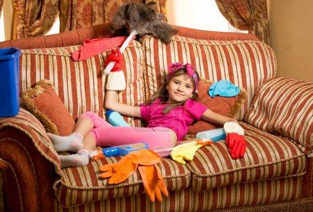 Photo pour Photo drôle de fille épuisée se détendre sur le canapé après le nettoyage de la maison - image libre de droit