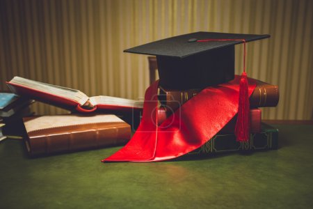 Toned photo of red ribbon and graduation cap on classic table