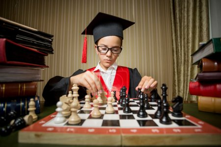 genius girl in graduation cap playing chess with herself