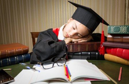 sleeping girl in graduation cap lying on table full of books