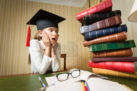 girl in graduation cap looking at high heap of books on table at