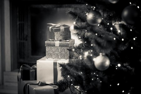 Photo for Closeup monochrome photo of Christmas gifts lying on floor next to decorated fir tree - Royalty Free Image