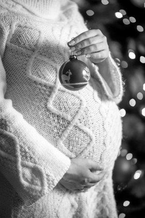 photo monochrome de femme enceinte posant avec boule de Noël