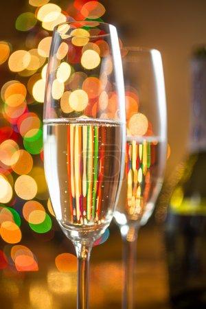 Photo pour Photo abstraite rapprochée de deux verres de champagne contre un sapin de Noël pétillant - image libre de droit