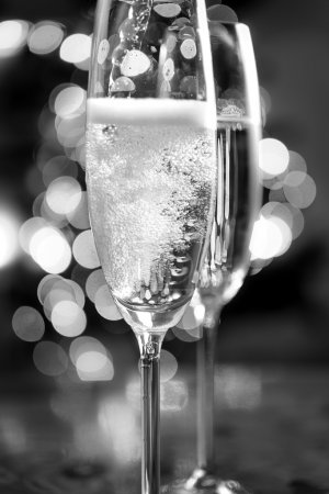 black and white photo of champagne poured into glasses