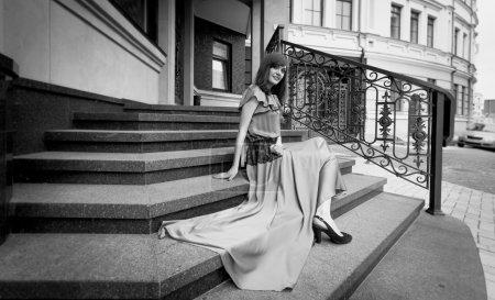 Foto de Foto blanco y negro de elegante mujer en vestido largo sentado en las escaleras de piedra - Imagen libre de derechos