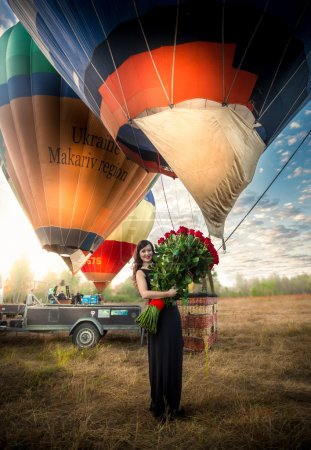 Woman posing with roses next to hot air balloon