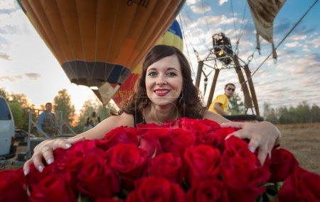 Photo pour Gros plan portrait de belle femme brune posant avec bouquet de roses contre des montgolfières - image libre de droit