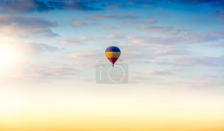 Colorful hot air balloon floating in the sky at sunrise