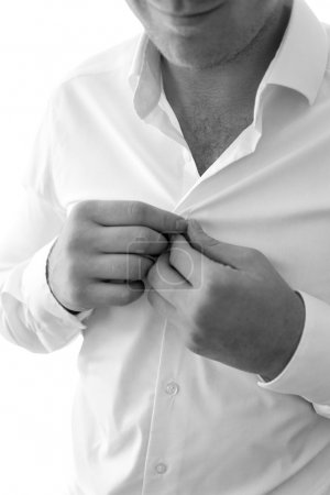 Black and white photo of young man putting on white shirt