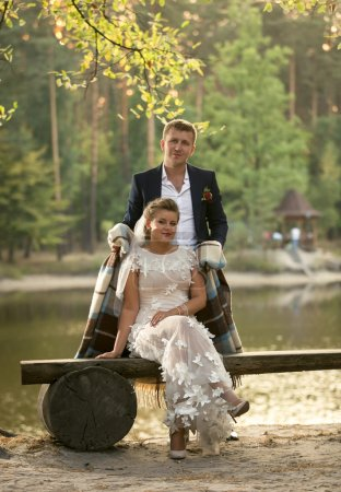 Toned photo of groom hugging bride sitting on bench at riverbank