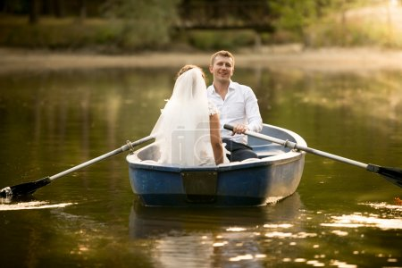Toned photo of just married couple having fun in the rowing boat