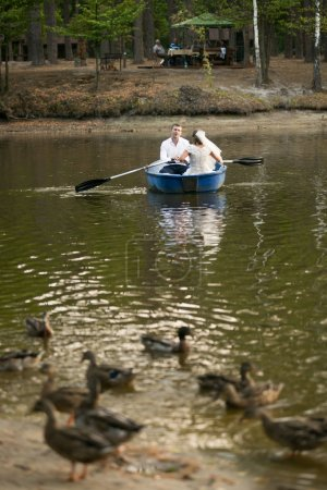 newly married couple riding on rowing boat on lake at forest
