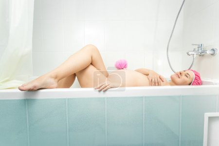 young pregnant woman lying in bath