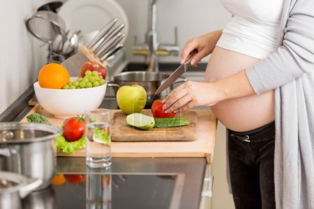 Closeup photo of pregnant woman cutting vegetables...