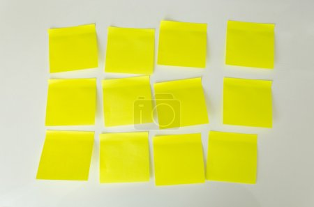 Photo for Closeup photo of 12 blank yellow sticky notes on white board - Royalty Free Image