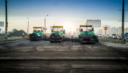 industrial machines laying asphalt on new road