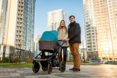 Happy family walking with pram on street at sunny day