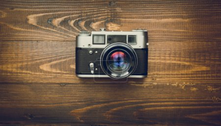 Toned image of old camera with manual lens on wooden background