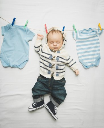 Photo for Funny photo of little baby boy in jeans hanging on cord next to drying clothes - Royalty Free Image