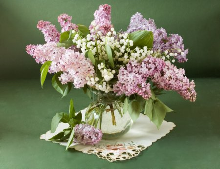 Still life with lilac flowers and lily of the valley in vase isolated on artistic background