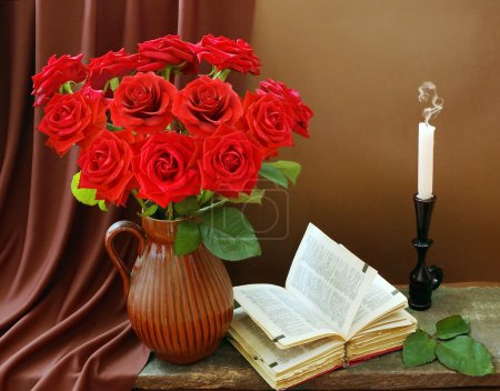 Still life with huge red roses bunch, open book and candle on artistic background