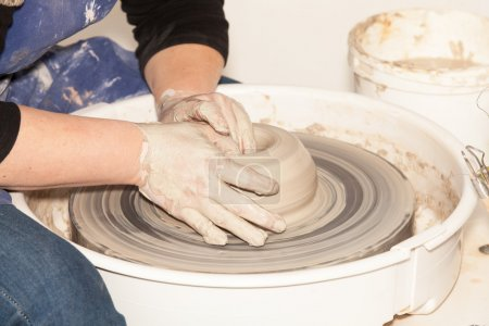 Photo for Female Potter creating a earthen jar on a Potter's wheel - Royalty Free Image