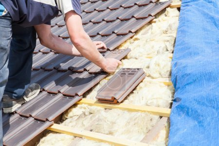 Roofer laying tile on the roof